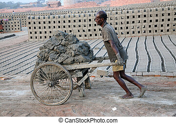Brick field. Laborers are carrying soil from the river and...