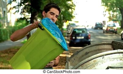 Throwing out thrash - Young caucasian man throwing out trash...