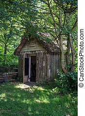 18th Century medieval woodcutters shed in woodland setting -...