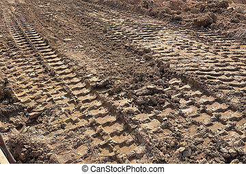 plowed field with tractor car tire track