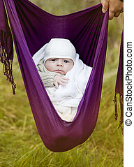 Baby hanging in sling - Cute newborn baby boy hanging in a...