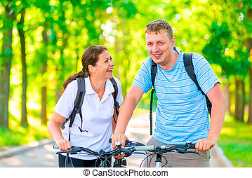 morning walk in the park on bicycles couples