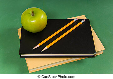 School books with green apple