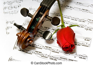 Violin, rose and sheet music - A violin peg-head, red rose...
