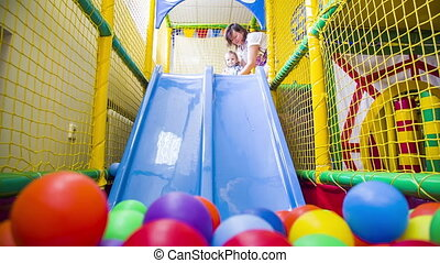 Small boy Sliding Into Multicolored Balls - Small happy boy...