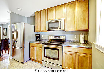 Kitchen cabinets and steel appliances - Light tones kitchen...