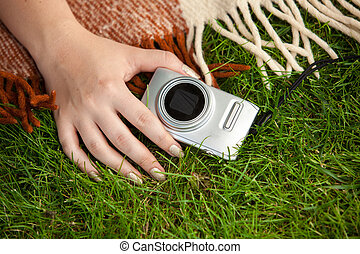photo of woman holding compact camera on grass - Closeup...