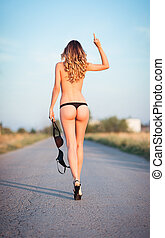 Sexy young woman going by the road and showing offensive...