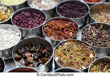 Different spices and herbs in metal bowls on a street market...