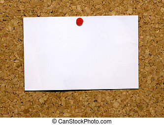 Small blank white business card attached to a cork notice board.