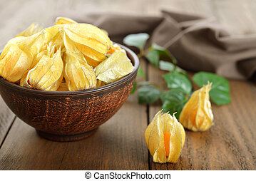 Physalis fruits in bowl closeup on wooden background