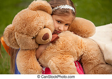 photo of sad little girl hugging teddy bear - Closeup photo...