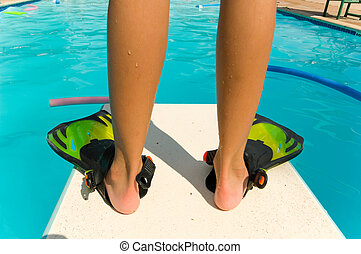 Diving Board - Child standiing with flippers on the end of a...
