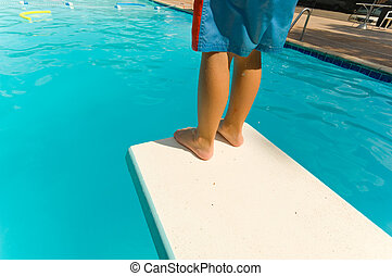 Child Swimming - Young boy standing on the end of a diving...
