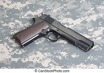 colt 1911 handgun on camouflage uniform