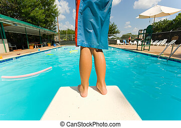 Apprehension - Young boy standing on the end of a diving...