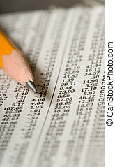 Stock Market Report - Yellow pencil on top of stock market...
