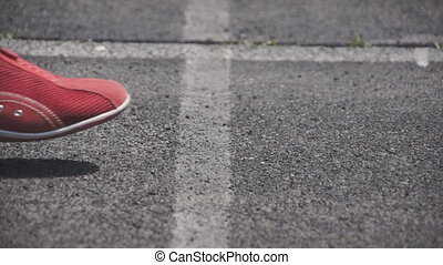 sports sneaker on the pavement - The stadium closeup foot...