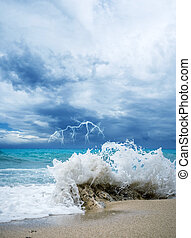 waves breaking on a stony beach during a thunderstorm with...