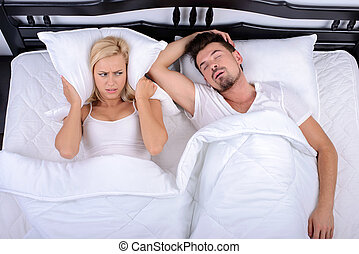 Couple in bed - Young woman can not sleep through the...