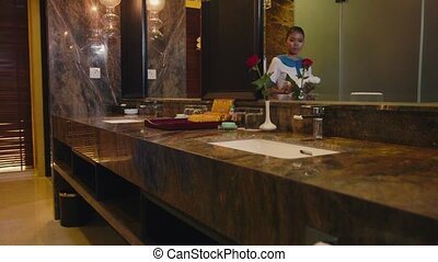 Maid cleaning hotel bathroom, job - Asian housekeeper...