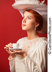 Portrait of redhead edvardian women with cup on red...