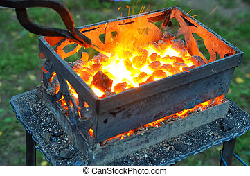 heating of the metal on the hot coals for forging on the...