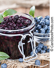 Portion of canned Blueberries on wooden background close-up...