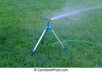 Mobile sprinkler system mounted on tripod working on fresh...