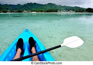 Young man kayaking in sea at over turquoise water during...