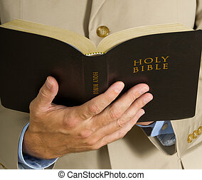 Man HOlding Bible - Man in business suit or preacher holding...