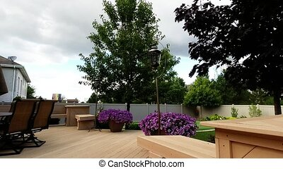 Backyard landscape - Trees and flowers blowing in wind
