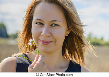 Portrait of young female with camomile