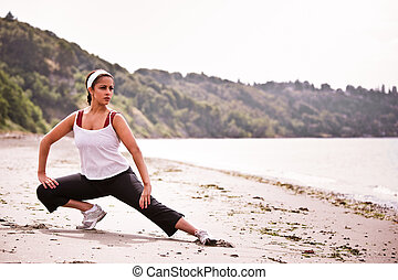 Sporty woman - A beautiful asian woman exercises at a beach