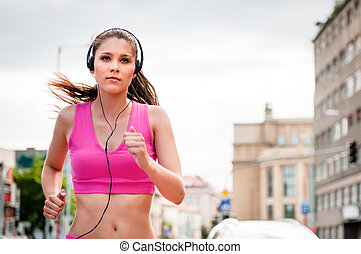 Jogging and listening music - Young beautiful woman with...
