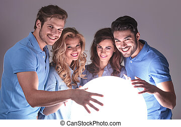 group of people with hands on big ball of light looking at...