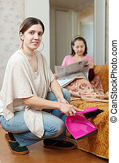Clean up woman, while mature mother reads newspaper - Clean...