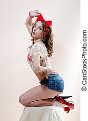 Awesome pinup pretty woman with red lips sitting on a chair...