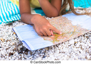 Adorable little girl with big map on tropical beach vacation...