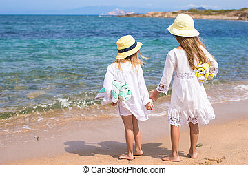 Adorable cute girls walking on white beach during vacation -...