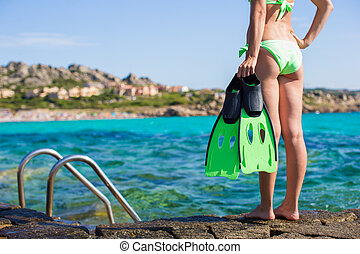 Beautiful young woman in bikini with snorkel equipment at...
