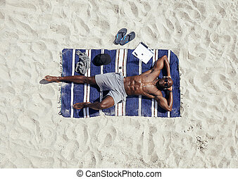 Man sunbathing on the beach - Top view of afro american...