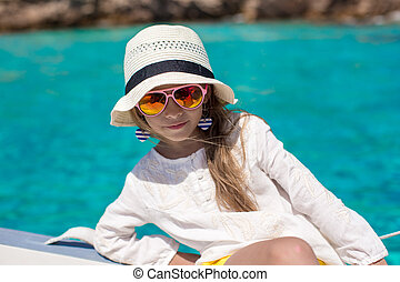 Beautiful little girl enjoying sailing on boat in the open sea