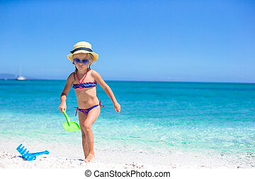 Adorable little girl playing with toy on beach vacation
