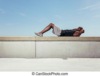 Muscular young man doing sit-ups