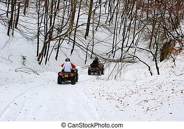ATV riders on winter forest road