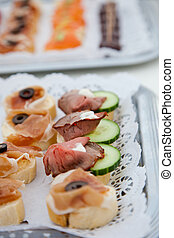 Canapes with assorted cold meat on a buffet