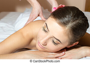 closeup on tired pretty woman lying on a table and taking beauty massages procedure