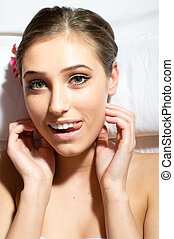 beautiful woman lying on a massage table showing tongue happy smiling and looking at camera closeup portrait