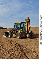Excavator on the Hill - A large yellow excavator sits...